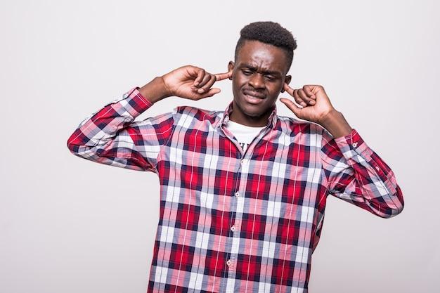Imagen de un joven africano disgustado que se encuentra aislado cierra los oídos de un ruido. Foto gratis