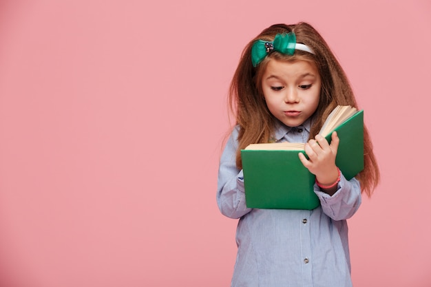 Imagen de linda chica con cabello castaño largo leyendo un libro interesante involucrado en la educación Foto gratis