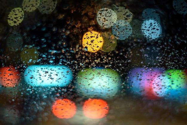 La imagen de la lluvia cae sobre la ventanilla del automóvil, la ciudad se ilumina por la noche con un dios abstracto de fondo. poca profundidad de campo, agarre, enfoque suave Foto Premium