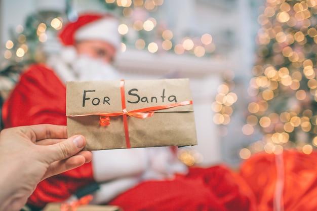 Imagen de la mano que sostiene la carta de santa. está cubierto con cinta roja. hay santa claus sentado y sosteniendo cartas. el los lee. Foto Premium