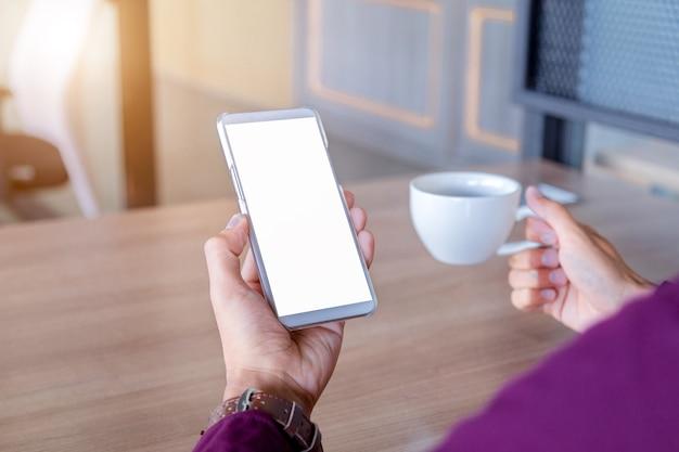 Imagen de maqueta de las manos del hombre sosteniendo un teléfono móvil blanco con tecnología de pantalla en blanco Foto Premium
