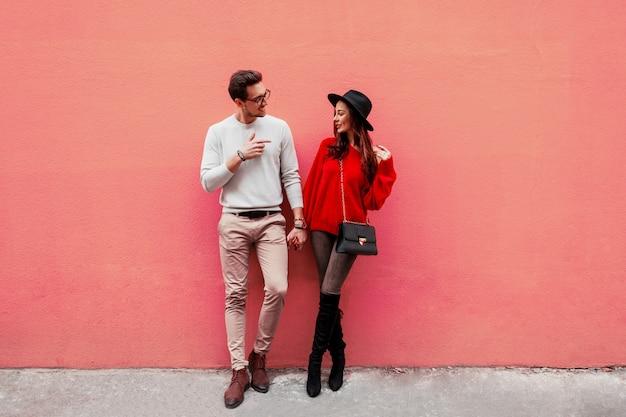 Imagen de moda de elegante elegante pareja de enamorados cogidos de la mano y mirándose con placer. mujer de pelo largo en suéter de punto rojo con su novio posando. Foto gratis