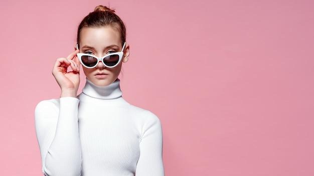 Imagen de moda de mujer elegante hermosa en golf de punto blanco y gafas de sol posando sobre pared rosa. Foto Premium