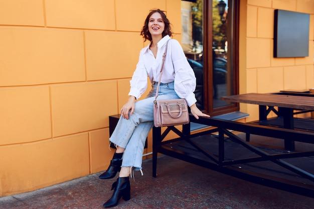 Imagen de moda de niña bonita morena con peinado corto en elegante blusa blanca casual y jeans. botas de cuero negro con tacones. chica sentada cerca de café moderno con paredes amarillas. Foto gratis