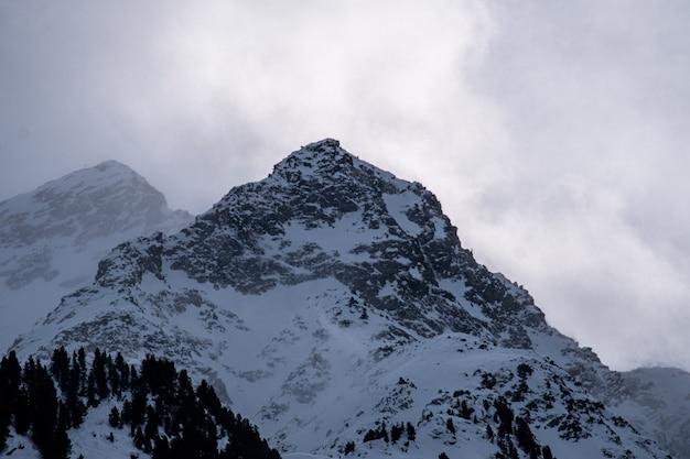 Imagen de montañas rocosas cubiertas de nieve bajo un cielo nublado y la luz del sol Foto gratis