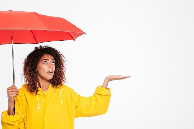 Imagen de mujer africana confundida en gabardina escondiéndose bajo paraguas y esperando raing sobre blanco Foto gratis