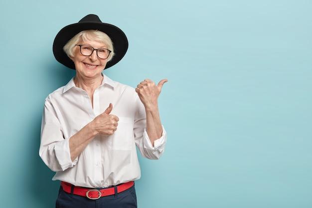 Imagen de mujer atractiva y arrugada con apariencia atractiva, se siente renovada, joven para su edad, señala en la esquina superior derecha, satisfecha con el producto, viste camisa blanca, tocado negro, anteojos ópticos Foto gratis