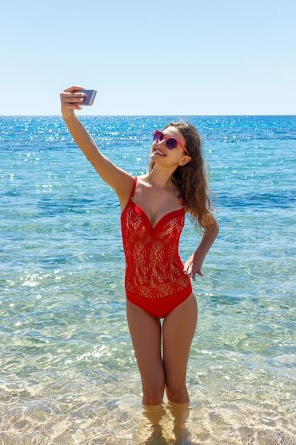 Imagen de mujer sonriente feliz usando la cámara del teléfono y haciendo selfie Foto Premium