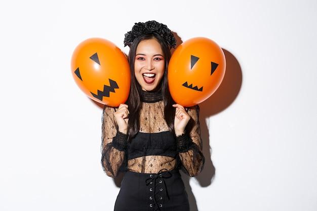 Imagen de niña asiática en traje de bruja malvada sosteniendo dos globos naranjas con caras aterradoras Foto gratis