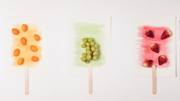 Imagen de paletas en palo sobre salpicaduras de acuarela Foto gratis