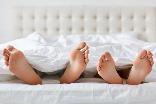 Imagen de los pies descalzos del hombre y de la mujer debajo de la manta en dormitorio. Foto gratis