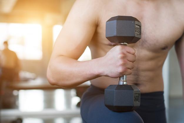 Imagen del primer del hombre que levanta pesas de gimnasia delante del fondo sucio de la pared en el gimnasio viejo. Foto Premium
