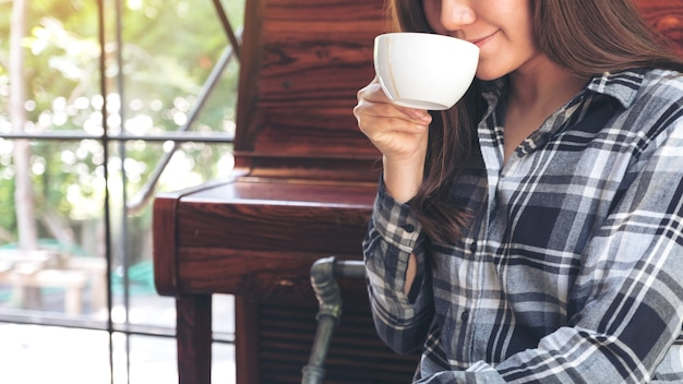 Imagen de primer plano de una mujer asiática sosteniendo una taza de café antes de beber Foto Premium