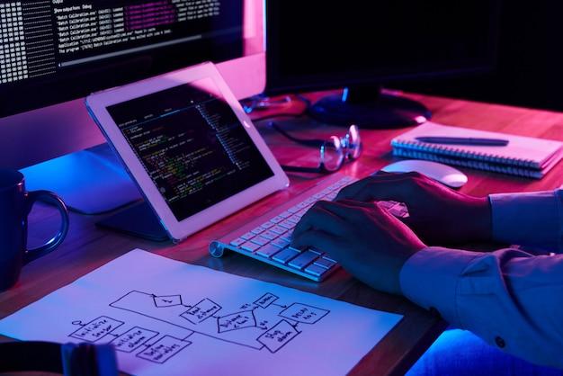 Imagen de primer plano del programador trabajando en su escritorio en la oficina Foto gratis