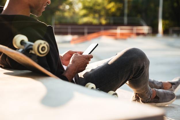 Imagen recortada de un chico africano usando un teléfono móvil Foto gratis