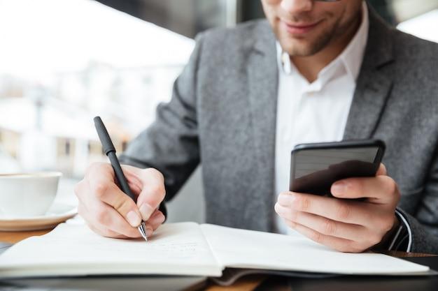 Imagen recortada del empresario tranquilo sentado junto a la mesa en la cafetería mientras usa el teléfono inteligente y escribe algo Foto gratis