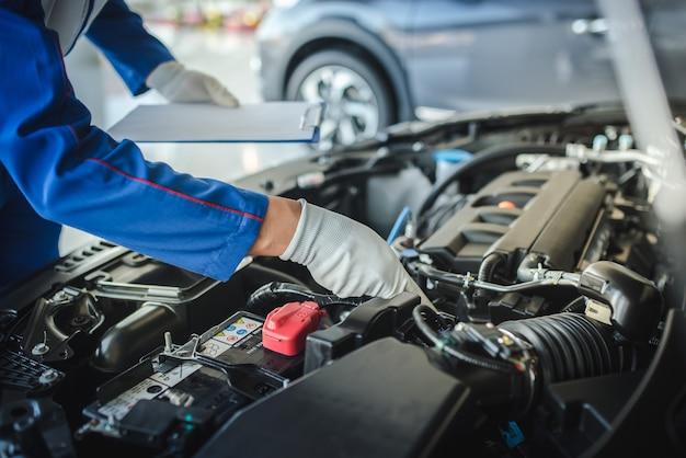 Imagen recortada de guapo mecánico en uniforme está trabajando en el servicio de automóviles. reparación y mantenimiento de automóviles. Foto Premium