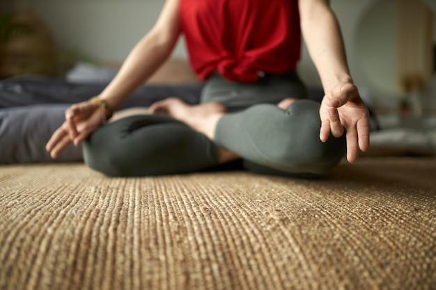 Imagen recortada de una mujer descalza en mallas sentada sobre una alfombra en postura de loto practicando la meditación para reducir el estrés, mejorar el enfoque y la atención. Foto gratis