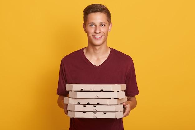 Imagen del repartidor hermoso alegre que lleva la camiseta casual de borgoña, sosteniendo la pila de cajas de pizza en las manos y mirando directamente a la cámara aislada en el estudio amarillo. concepto de comida chatarra. Foto gratis