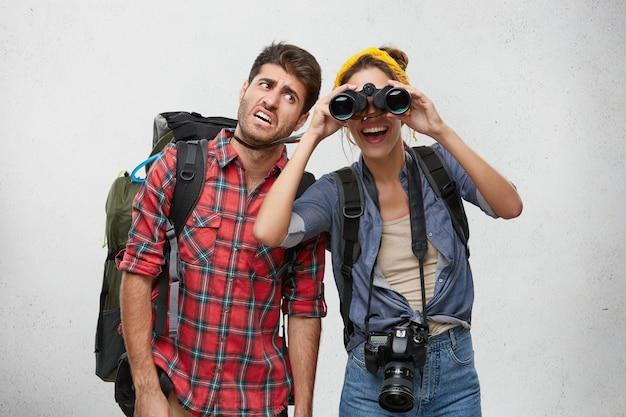 Imagen del turista cansado del hombre barbudo que lleva la mochila pesada y de la mujer emocionada alegre con la cámara de la foto que busca el lugar para acampar usando binocular durante el viaje que camina juntos. personas y aventura Foto gratis