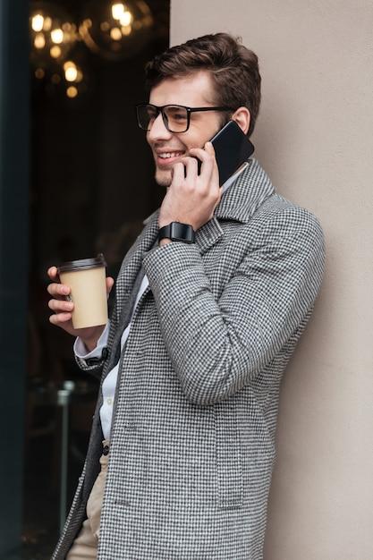 Imagen vertical del empresario sonriente en anteojos y abrigo Foto gratis