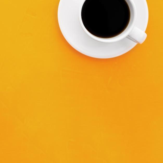 Imagen de la vista superior de la taza de café sobre fondo amarillo de madera Foto gratis