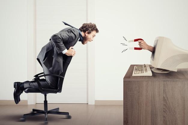 El imán atrae a un hombre a una computadora. captando personas con marketing Foto Premium