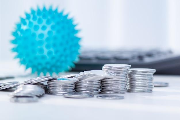 Impacto del coronavirus en la economía. monedas, calculadora en el escritorio. concepto de medicina y dinero, gastos para covid-19. Foto Premium