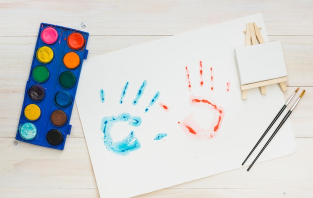 Impresión azul y roja de la mano en la hoja blanca con equipo de pintura sobre superficie de madera Foto gratis