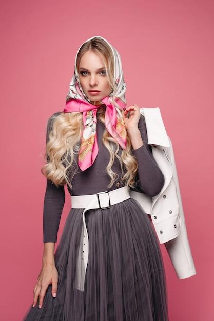 Impresionante belleza rusa en velo. ella está sosteniendo una chaqueta de cuero blanco en su brazo detrás de su espalda. aislar en rosa. Foto Premium