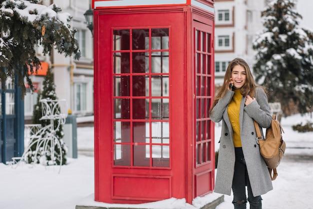 Impresionante mujer morena en cardigan amarillo de pie junto a la cabina de llamada británica en día de invierno. foto exterior de mujer adorable en abrigo de moda posando junto a la cabina telefónica Foto gratis