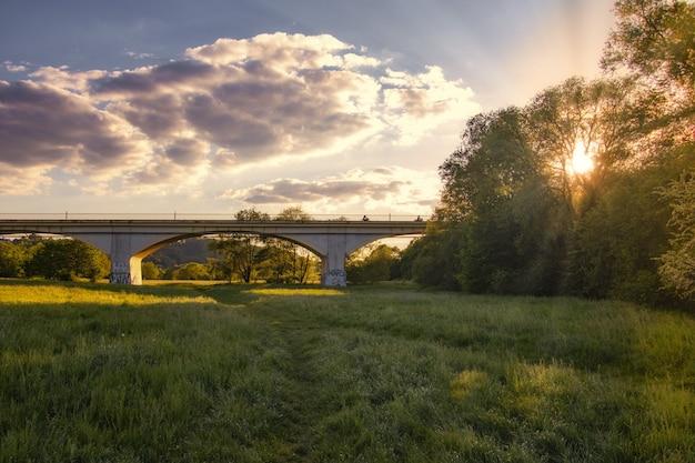 Impresionante puesta de sol sobre un bosque verde con un largo puente en el medio Foto gratis