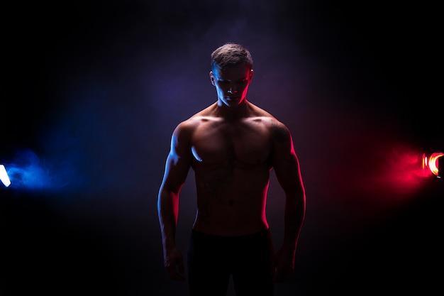 Impresionante silueta culturista. culturista atlético guapo guapo. cuerpo musculoso fitness sobre fondo de humo de color oscuro. hombre perfecto tatuaje, posando. Foto Premium