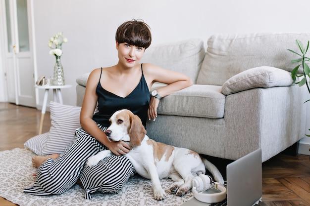 Increíble dama morena lleva elegante reloj de pulsera posando junto al sofá acariciando lindo beagle Foto gratis