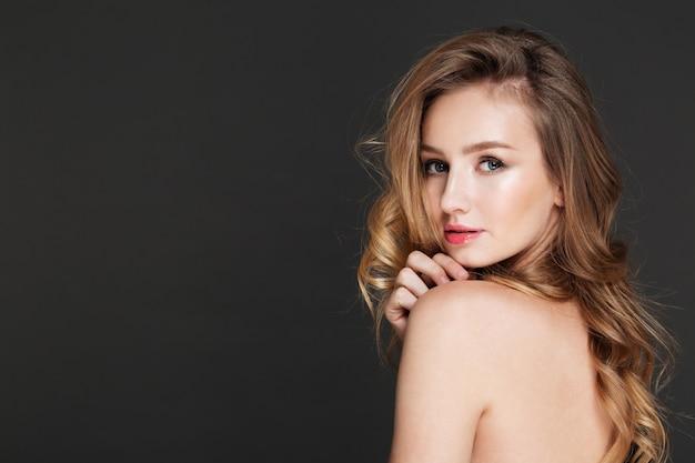 Increíble mujer joven posando sobre pared gris Foto gratis