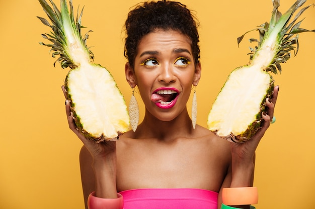 Increíble mujer mulata con maquillaje colorido mirando hacia arriba y lamiéndose los labios mientras sostiene dos partes de piña madura apetitosa aislada, sobre amarillo Foto gratis