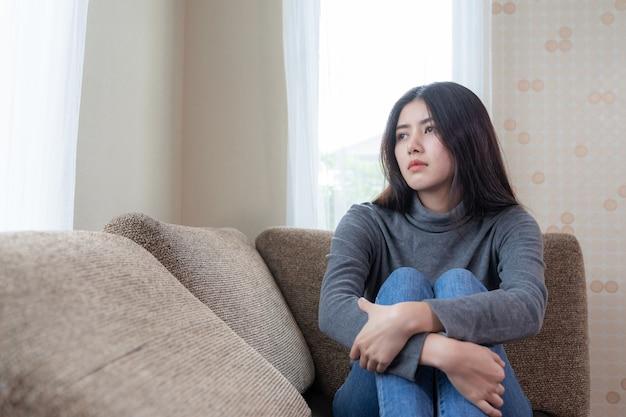 Infeliz mujer asiática bastante joven emplazada sola en el sofá con tristeza Foto gratis
