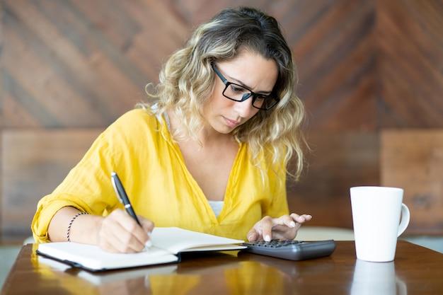 Infeliz mujer joven haciendo cálculos y tomando notas Foto gratis