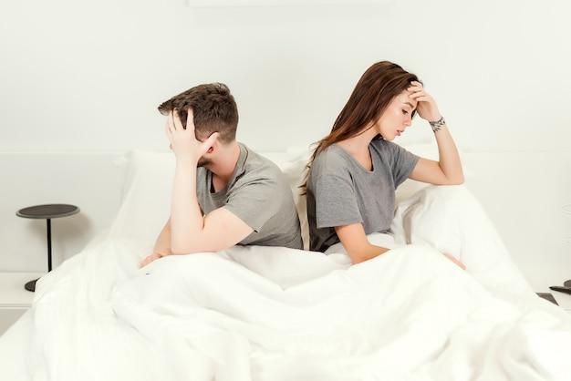 Infeliz pareja en la cama, sin mirarse y peleando. Foto Premium