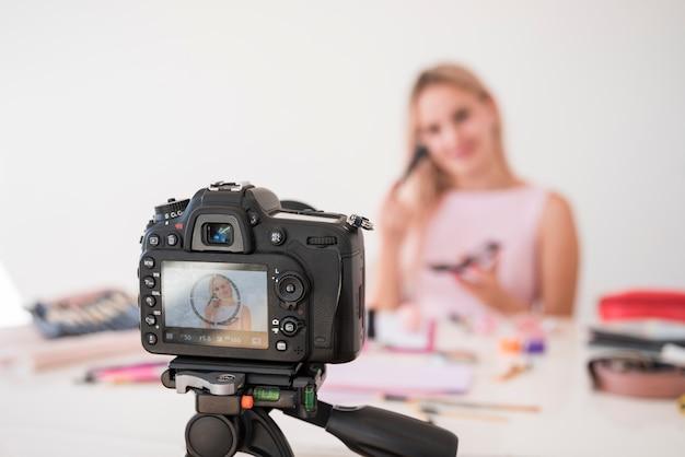 Influencer rubia grabando vídeo de maquillaje Foto gratis