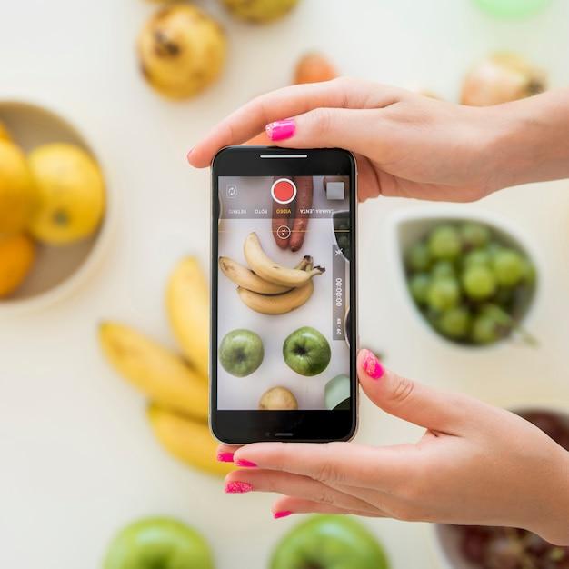 Influencer rubia haciéndole foto a fruta Foto gratis