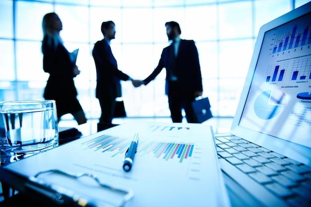 Información económica con ejecutivos negociando de fondo Foto gratis