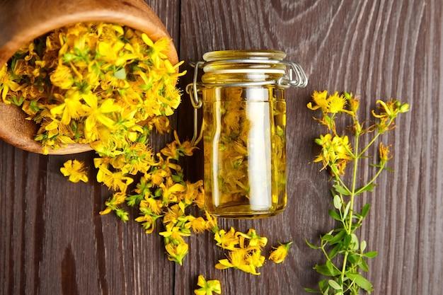 Infusión de hierbas de hypericum perforatum o hierba de san juan con flores frescas en la mesa de madera Foto Premium