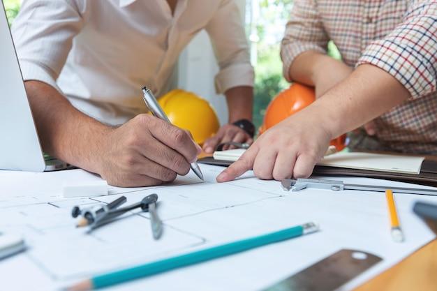 Ingeniero arquitectos y equipo de oficina de agente de bienes raíces trabajando con planos Foto Premium