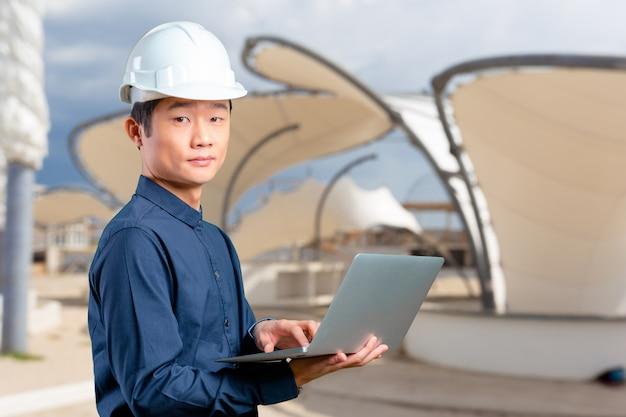 Ingeniero asiático del hombre con el ordenador portátil Foto Premium