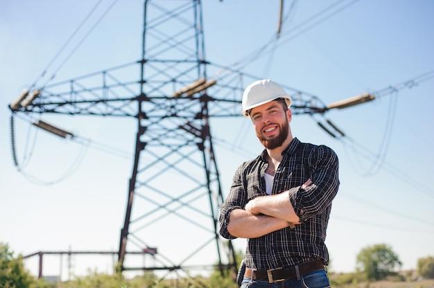 Ingeniero con casco blanco debajo de las líneas eléctricas. ingeniero de trabajo Foto Premium