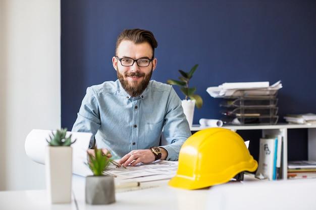Ingeniero civil sonriente trabajando en plano en el lugar de trabajo Foto gratis