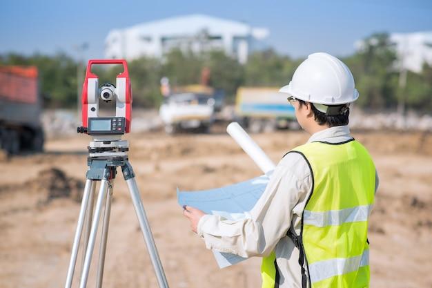 Ingeniero de construcción que controla el dibujo de construcción en el área del sitio Foto Premium