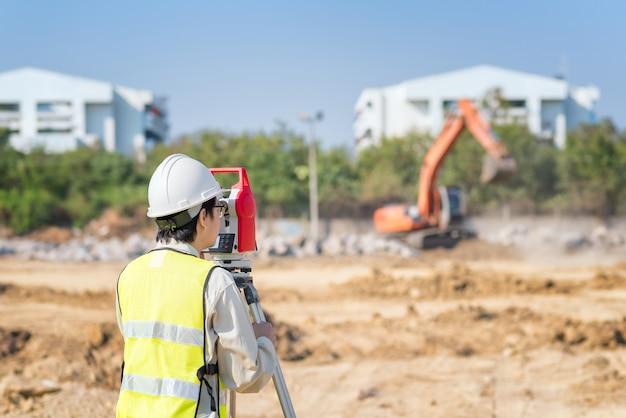 Ingeniero de construcción, uso de equipo de topógrafo, control de obra Foto Premium