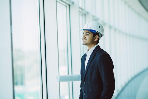 Ingeniero contratista de sitio masculino indio con casco con papel de impresión azul caminando en el sitio de construcción Foto gratis